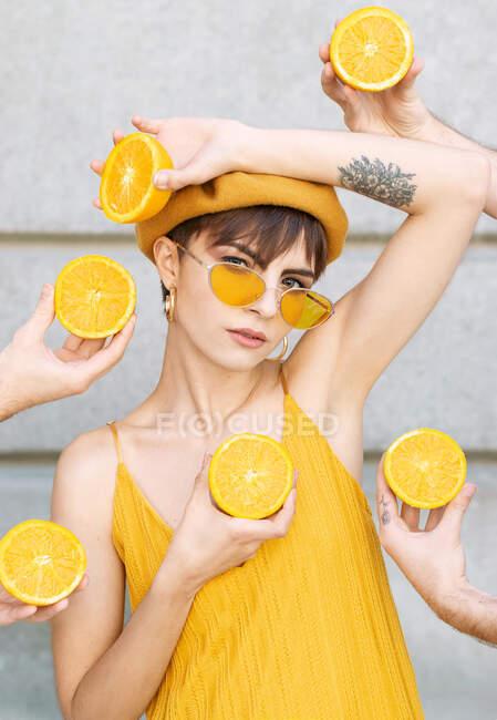 Joven hembra en gafas de sol amarillas de moda y boina mirando a la cámara mientras está de pie en medio de la cosecha irreconocibles manos de personas con naranjas a la mitad contra la pared de la construcción en la calle de Madrid - foto de stock