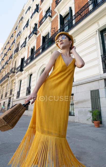 Низкий угол стройная молодая стильная женщина в модном желтом наряде размахивая юбкой платья во время танцев на улице в солнечный день в Мадриде — стоковое фото