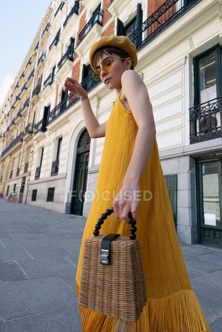 Low angle of slim young stylish woman in trendy yellow outfit waving skirt of dress while dancing on street on sunny day in Madrid — Stock Photo