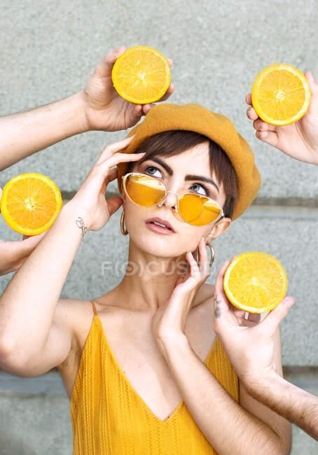 Молодая женщина в модных желтых солнцезащитных очках и берете трогательное лицо и глядя вверх, в то время как стоя среди урожая неузнаваемых людей руки с наполовину апельсины против стены здания на улице Мадрид — стоковое фото