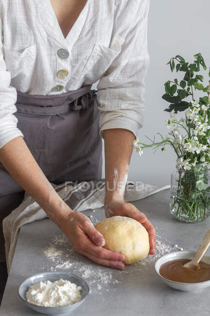 Anonymous female baker in apron kneading soft dough with flour on table near apple sauce and bouquet of flowers while cooking pastry — Stock Photo