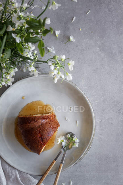 Top view of delicious Bundt cake with apple sauce placed on table near white flowers and burning candle — Stock Photo