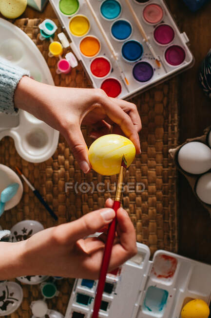 Pessoa irreconhecível em suéter cobrindo ovos de galinha frescos com tinta amarela enquanto se prepara para a celebração da Páscoa — Fotografia de Stock