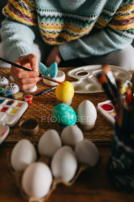Unrecognizable person in sweater covering fresh chicken eggs with yellow paint while preparing for Easter celebration — Stock Photo