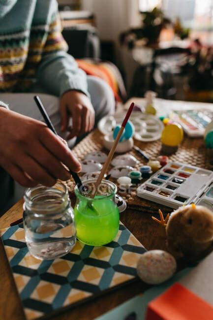 Неузнаваемый человек моет кисть в воде, сидя рядом со столом и рисуя пасхальные яйца дома — стоковое фото