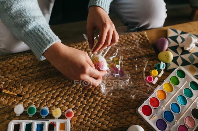 De cima pessoa anônima envolvendo ovo em filme para fazer ornamento sobre a mesa enquanto se prepara para a celebração da Páscoa em casa — Fotografia de Stock