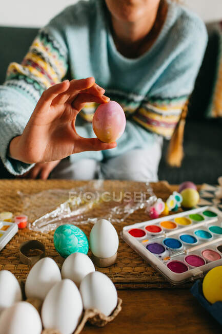 Cropped anonymous person demonstrating finished Easter egg over table with watercolor at home — Stock Photo