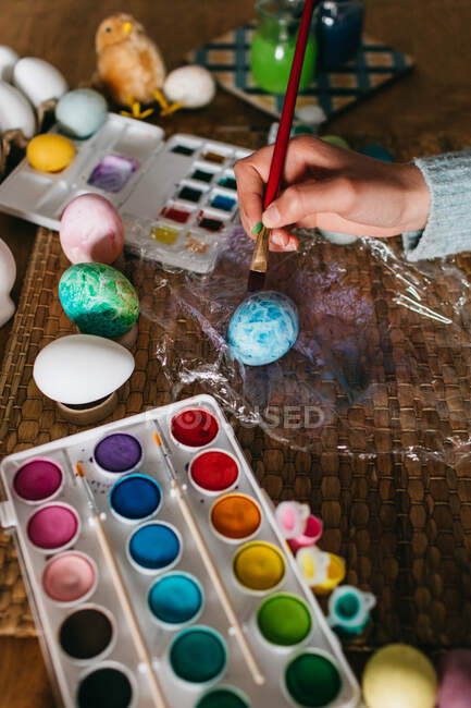 Unrecognizable person in sweater covering fresh chicken eggs with blue paint while preparing for Easter celebration — Stock Photo