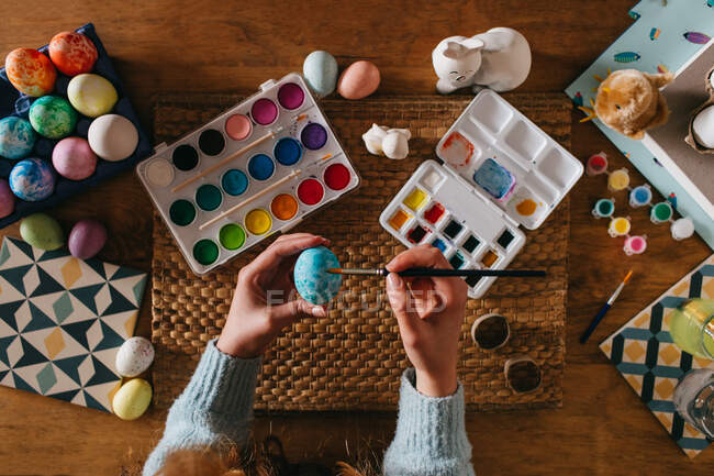 From above top view of cropped unrecognizable person in sweater covering fresh chicken eggs with blue paint while preparing for Easter celebration — Stock Photo
