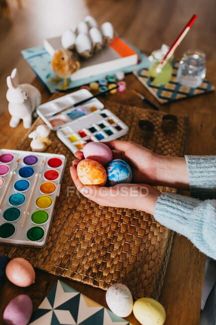 From above cropped anonymous person demonstrating finished Easter egg over table with watercolor at home — Stock Photo