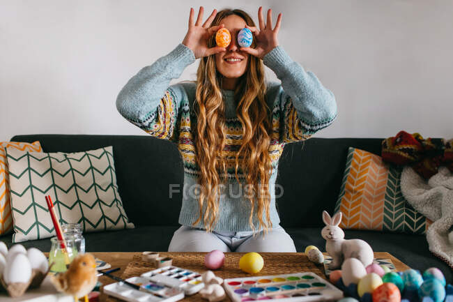 Cheerful female in ornamental sweater smiling and keeping colored Easter eggs near eyes while sitting on chair and preparing for Easter celebration at home — Stock Photo
