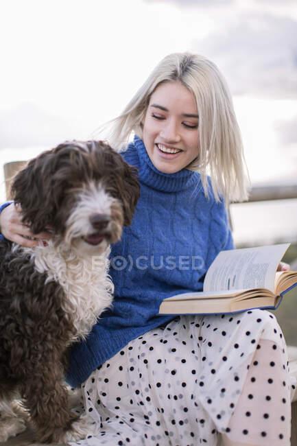 Junge Frau in blauem Pullover und Rock sitzt auf Holzbank und streichelt Hund, während sie sich mit Buch am Meer ausruht — Stockfoto