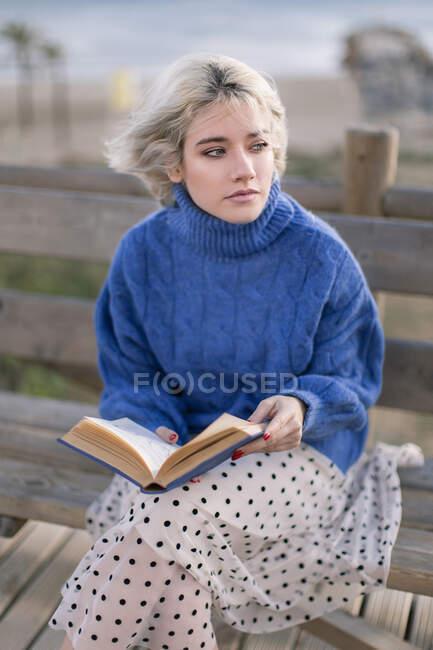 Молода блондинка в теплому синьому светрі і спідниці, що відвернулася, сидячи на дерев'яній лавці на терасі проти розмитого пляжу і читаючи книжку — стокове фото