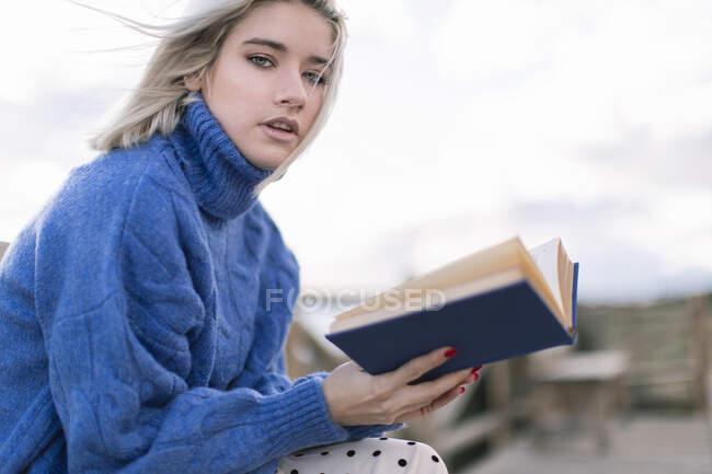 Бічний погляд на молоду блондинку в теплому синьому светрі і спідницю, яка дивиться на камеру, сидячи на дерев'яній лавці на терасі з розмитим фоновим читанням книги — стокове фото