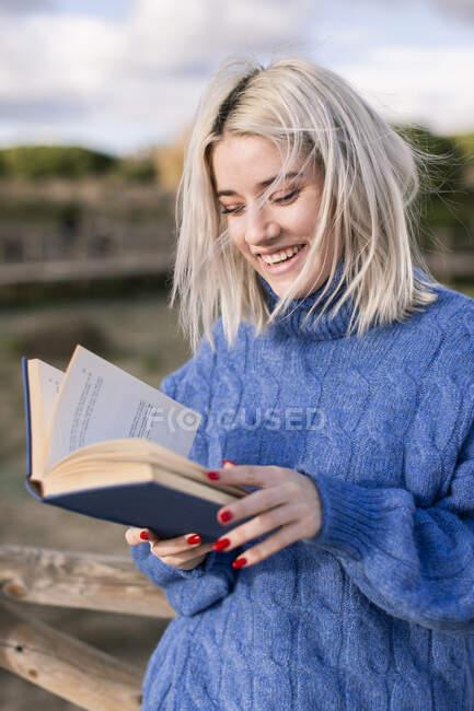 Jovem mulher loira alegre em suéter azul quente apoiando-se na cerca de madeira e livro de leitura enquanto passa o dia de primavera no campo — Fotografia de Stock