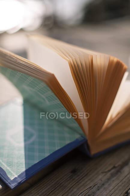 З верхньої кімнати відкритої книги з жовтими сторінками і синім покриттям, поміщеним на дерев'яній лавці в сонячний день. — стокове фото