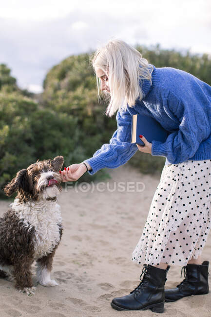 Side view of happy young female in casual sweater and skirt holding book and stroking adorable curly dog while spending free time on sandy beach with green plants in background — Stock Photo