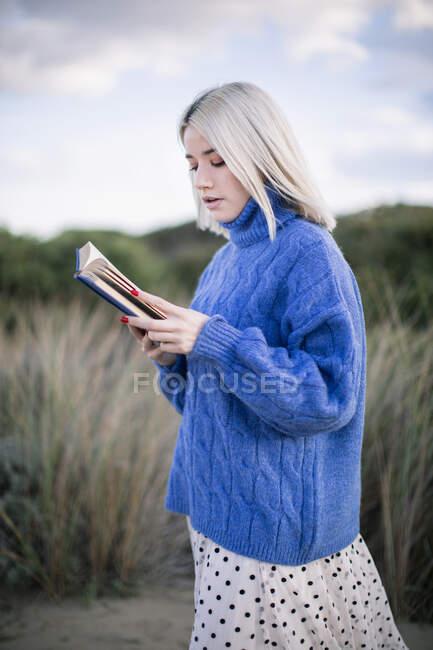 Задумчивый вид на молодую женщину с светлыми волосами в тёплом голубом свитере, держащую открытую книгу, читающую, стоя на размытом естественном песчаном фоне — стоковое фото