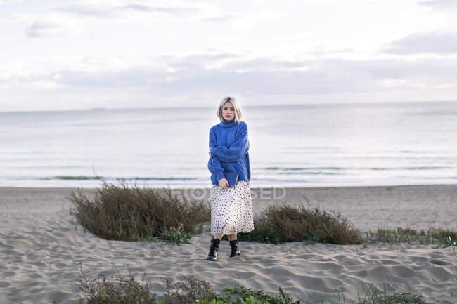 Jovem mulher pensativa com cabelo loiro em suéter azul quente segurando livro e olhando para a câmera enquanto está de pé contra fundo arenoso oceano — Fotografia de Stock