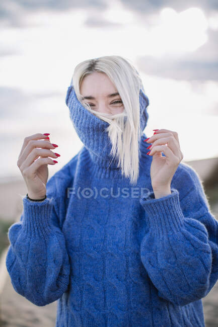 Joyful cheerful young blonde female in blue knitted sweater looking at camera and laughing while standing against blurred background of sea coast — Stock Photo