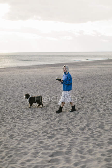 Seitenansicht einer jungen Frau in stylischem Outfit, die mit aufgeschlagenem Buch in der Hand am leeren Sandstrand an bewölkten Tagen mit treuem netten Buch spaziert — Stockfoto