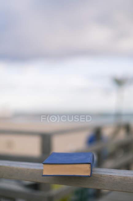 De cima livro fechado com tampa azul colocada em cerca de madeira em dia ensolarado com praia no fundo — Fotografia de Stock