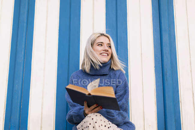 From below happy young female in warm sweater and skirt sitting with open book reading against white and blue striped wall — Stock Photo