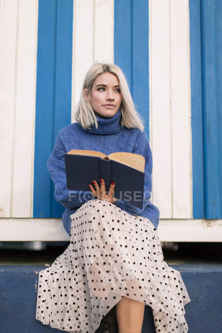 From below thoughtful young female in warm sweater and skirt sitting with open book reading against white and blue striped wall looking away — Stock Photo