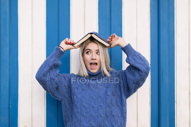 Funny astonished young female in casual knitted sweater holding open book on head and looking away while standing against colorful wall — Stock Photo
