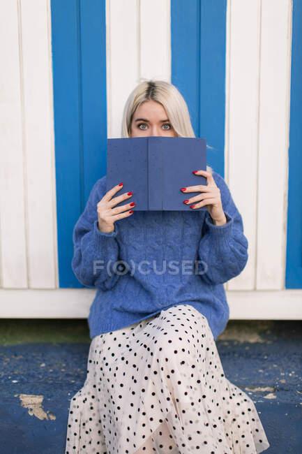 Смешная удивленная молодая женщина в случайном вязаном свитере, держащая открытую книгу, закрывающую рот, и смотрящая на камеру, стоя у разноцветной стены — стоковое фото