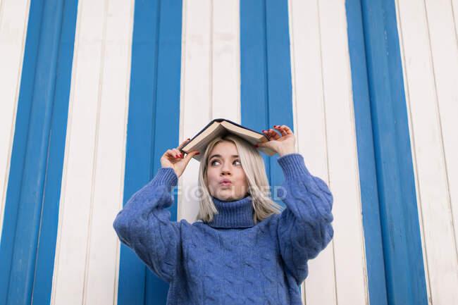 Divertente stupito giovane donna in maglione casual maglia tenendo aperto il libro sulla testa e guardando lontano mentre in piedi contro parete colorata — Foto stock