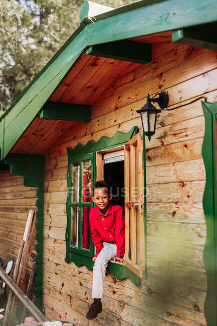 Cheerful black child in red shirt and white pants looking at camera through open window of rural wooden house — Stock Photo