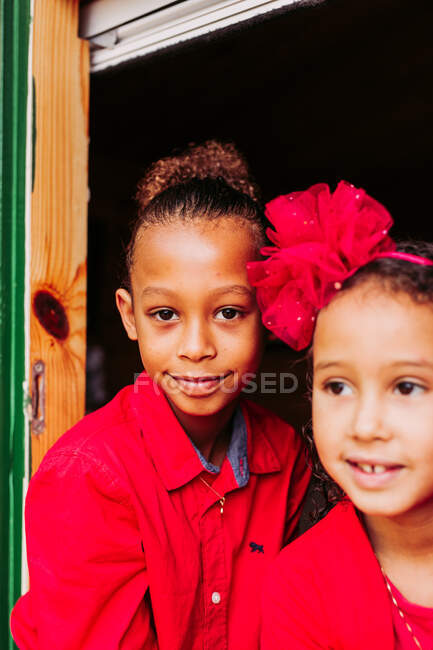 Cute black little siblings smiling and looking at camera through open window of wooden cabin — Stock Photo