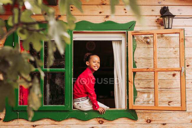 Cheerful black child in red shirt and white pants looking through open window of rural wooden house — Stock Photo