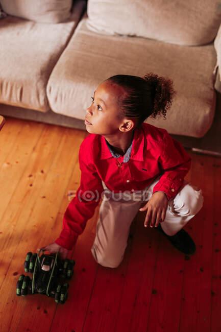 D'en haut de mignonne petite fille ethnique aux cheveux bouclés avec arc rouge portant une robe rouge regardant la caméra et souriant sur fond flou — Photo de stock