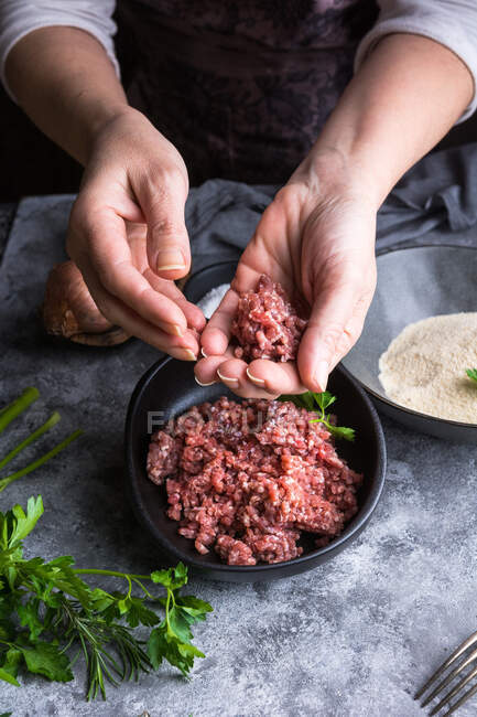 From above unrecognizable person wearing apron showing meatball to camera over bowls with minced meat during lunch preparation — Stock Photo