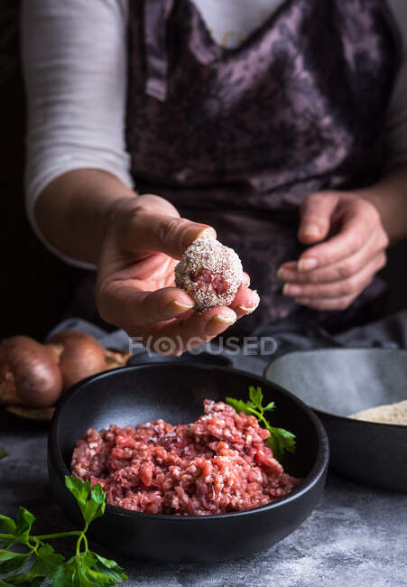 From above unrecognizable person wearing apron showing meatball to camera over bowls with minced meat and bread crumbs during lunch preparation — Stock Photo