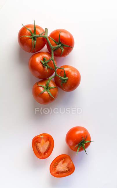 Зверху можна побачити достиглі цілі й наполовину поміщені помідори на білому тлі. — стокове фото