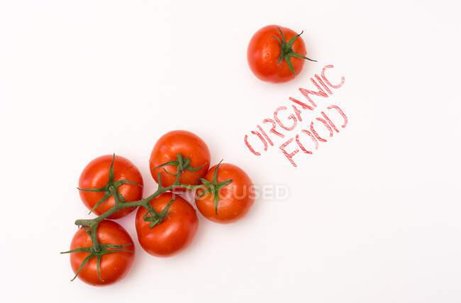 З верхнього виду чистий дозрілий помідор, поміщений біля органічного письма на задньому плані. — стокове фото