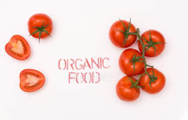 Dall'alto vista pulito pomodoro maturo posto vicino alimenti biologici scrivendo su mentre sfondo — Foto stock