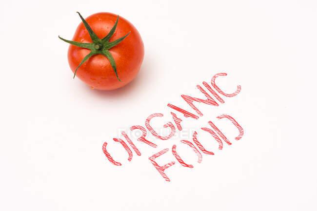С верхней точки зрения чистый спелый помидор помещен рядом с органической пищей на фоне — стоковое фото