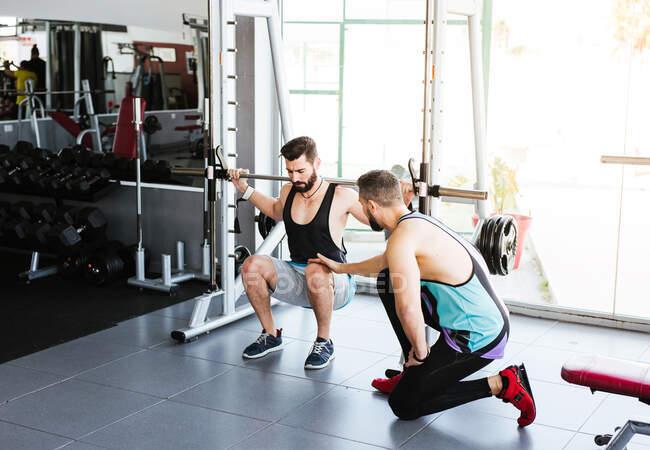 Мощный целеустремленный спортсмен делает упражнения с штангой на корточках во время тренировки тяжелой атлетики с личным тренером в современном тренажерном зале — стоковое фото