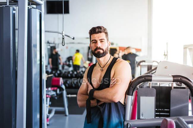 Мускулистый бородатый мужчина в спортивной одежде смотрит в камеру, стоя со скрещенными руками и опираясь на спортивный инвентарь в легком современном спортзале — стоковое фото