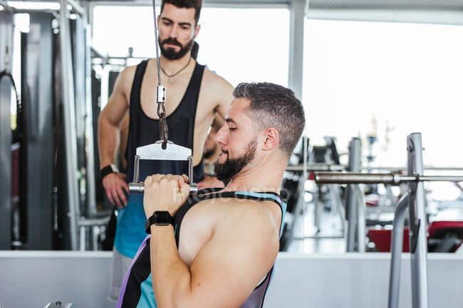 Уверенный инструктор помогает усердному клиенту в спортивной одежде, выполняя упражнения на весовой машине, стоя против размытого интерьера современного спорткомплекса — стоковое фото