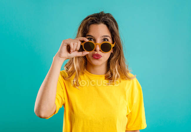 Молодая женщина в желтом наряде смотрит в камеру и настраивает стильные солнцезащитные очки на цветном бирюзовом фоне — стоковое фото