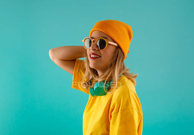 Side view of happy young cute female in yellow outfit and orange beanie looking away wearing sunglasses sunglasses against colorful turquoise background — Stock Photo