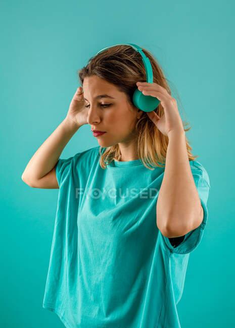 Вид сбоку симпатичной молодой женщины в яркой футболке, отводящей взгляд, слушая музыку в наушниках на бирюзовом фоне — стоковое фото