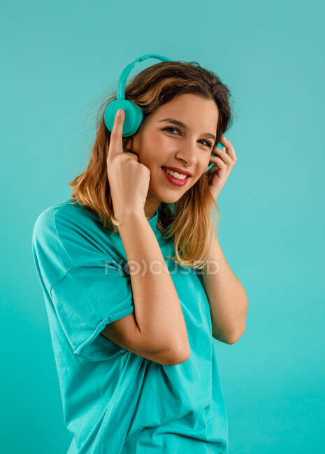 Side view of happy young woman in bright t shirt smiling looking at camera and listening to music in earphones against turquoise background — Stock Photo