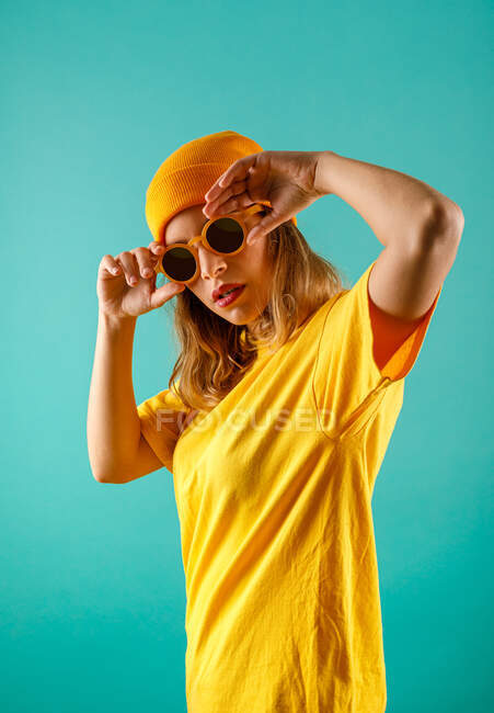 Young female in yellow outfit looking at camera and adjusting stylish sunglasses against turquoise background — Stock Photo
