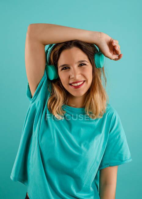 Счастливая молодая женщина в яркой футболке улыбается, глядя в камеру и слушая музыку в наушниках на бирюзовом фоне — стоковое фото